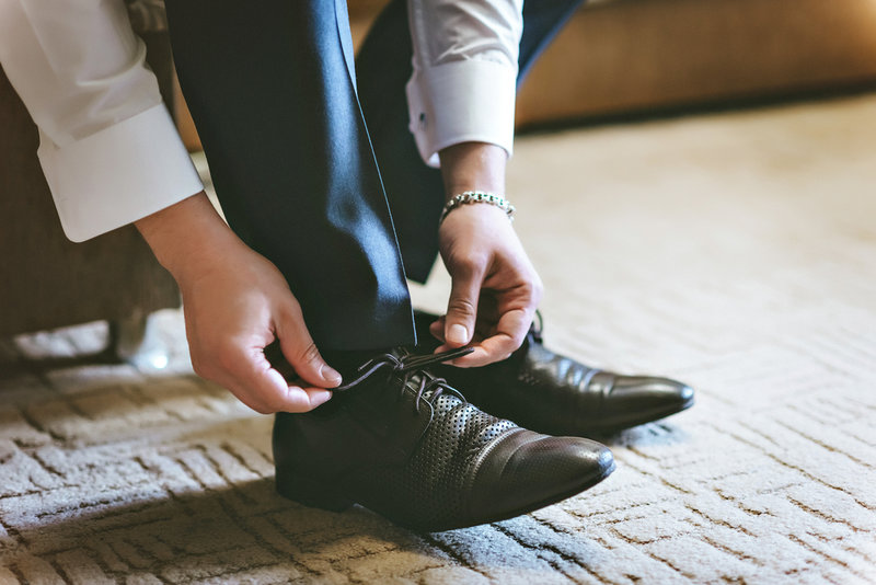 man putting shoes on before returning to work